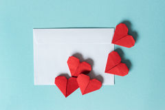 White paper envelope and red origami hearts on a blue background. Top view. The concept of Love At A Distance royalty free stock photo