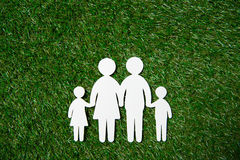 White paper figures of family on grass meadow. Top view of white paper figures of family on grass meadow stock images
