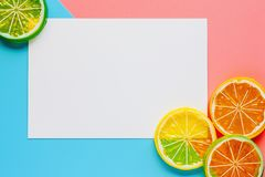 White paper frame with lemon slice on pink and blue pastel color. Background. Flat lay and top view image royalty free stock photos