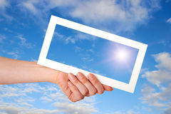 White paper frame in woman hand on blue sky Stock Photo