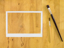 White paper frame on wood background. White paper frame on wood background with paintbrush stock photos