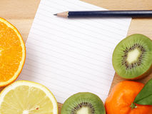 White paper with fruit  border and blue pencil Stock Photos