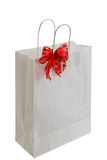 White paper gift bag with red ribbon Royalty Free Stock Photos