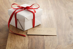 White paper gift box with thin red ribbon and i love you paper card on old wood table Royalty Free Stock Image