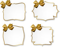 White paper gift cards with golden satin bows. Stock Photos