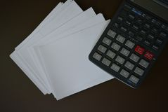 White paper with gray calculator and a yellow pen on a brown matte background. Excellent bright photos for stores for articles and magazines and any glosses made royalty free stock photography