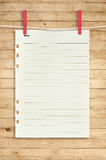 White paper hanging on the clothesline and red clip on vintage wood Royalty Free Stock Image
