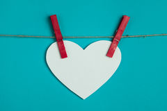 White paper heart attached to a rope with red pins Stock Photography