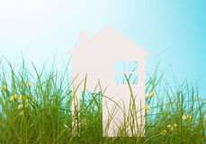 White paper house in green grass over blue sky Stock Images