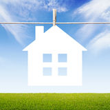 White paper house. Icon hanging on clothespin Royalty Free Stock Photo