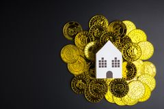 White paper house toy on Cryptocurrency golden bitcoins coin on. Black background with copy space.Real estate concept, New house concept, Finance loan business Stock Photos