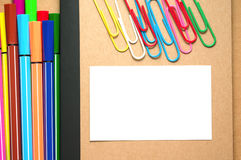 White paper on kraft notebook with markers and clips Royalty Free Stock Photo