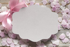 White paper label, pink bow and pink hearts in background Stock Photos