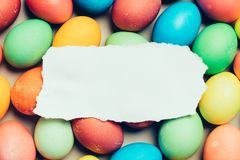 White paper laying on top of colorful eggs. Piece of plain white paper laying on the top of colorful eggs. Easter. Copyspace Royalty Free Stock Images