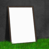 White paper lean on black wall on the grass floor,white Mock up. For your content Stock Image