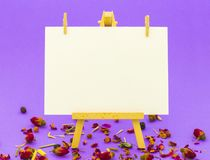 White paper on little easel on colorful background. White paper on little easel on colorful violet background with little roses Royalty Free Stock Photo