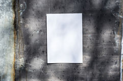 White paper on metal wall. White paper on a metal wall, in sunshine, ideal for poster mock up Royalty Free Stock Photography