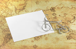 White paper and mini bicycle on a old world map Stock Photography