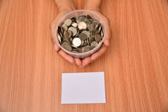 White paper mock up and stack coins in glass put on hand for sav Royalty Free Stock Image