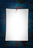White paper note. With put pin on blue grunge background stock images