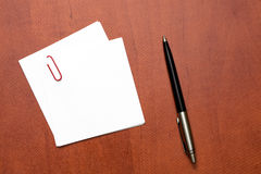 White paper note with a clip and pen Royalty Free Stock Photo