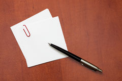 White paper note with a clip and pen. Over the wooden background Stock Photo