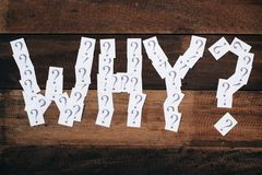 White paper note with question mark arranged to make a WHY word on wooden table Stock Photo