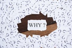 White paper note with question mark and word WHY in the center on wooden table Stock Photos