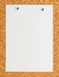 White paper note sheet with blue push pin on cork board Stock Image