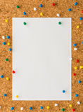 White paper note sheet with multicolored push pin on cork board Stock Photos