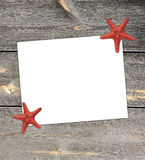 White paper note with starfish in the summer vacation season. White blank paper with starfish on wooden background summer beach season Stock Photo