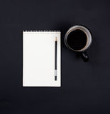 White paper notepad and a cup of coffee on black chalkboard back Stock Images