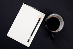 White paper notepad and a cup of coffee on black chalkboard back Royalty Free Stock Photos