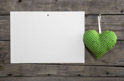White paper on an old wooden wall with a lime green hanging hear Royalty Free Stock Photography