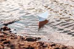 White paper origami boat on the river. Summer day royalty free stock images