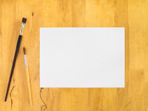 White paper with paintbrush on wood background. White paper with paintbrush on wood background, Blank paper stock images