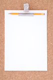 White Paper, Paperclip and Pencil over cork surfac Royalty Free Stock Image