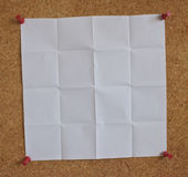 White paper on a peg board. A piece of white paper pinned to a peg board royalty free stock images
