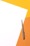 White paper and pen on yellow brown background Royalty Free Stock Photos