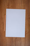 White paper and pencil on wood table. A white paper and pencil on wood table Stock Image