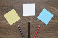 White paper and pencil on wooden table. Work space table with papers and pencil on wood background Stock Photos