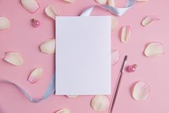White paper with pink petals on pastel background. Stock Photo