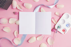 White paper with pink petals on pastel background. Stock Image