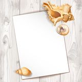 White paper pinned seashells on a background of wood t Royalty Free Stock Photography