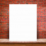 White paper poster lean at brick wall and wood table. Blank white paper poster lean at brick wall and wood table. For text input or according to your design Stock Photos