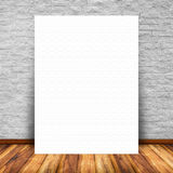 White paper poster lean at interior with brick wall. Blank white paper poster lean at brick wall and wood floor. For text input or according to your design Royalty Free Stock Photo
