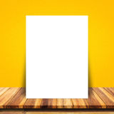 White paper poster lean at yellow wall and wood table. Blank white paper poster lean at yellow wall and wood table. For text input, or according to your design Royalty Free Stock Photos
