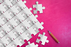 White paper puzzle pieces on pink leather background.jpg Stock Images