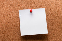 White paper with red clip nailed on wooden board Royalty Free Stock Images