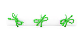 White paper scroll tied with cord, three green knots.  stock photography